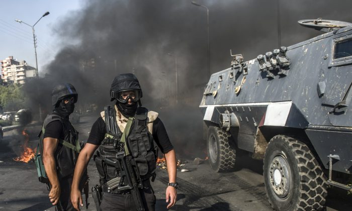 Egyptian riot policemen secure a street near an armoured vehicle during a rally of supporters of the Muslim Brotherhood movement to mark the first anniversary of the military ouster of president Mohamed Morsi on July 3, 2014 in Cairo's Ain Shams district. Egyptian police swiftly quashed Islamist protests firing tear gas and arresting dozens of demonstrators, as the protests are seen as a test of the Islamists' strength, with the Muslim Brotherhood-led Anti Coup Alliance having issued an aggressive rallying cry demanding a 'day of anger' to mark Morsi's overthrow. (Khaled Desouki/AFP/Getty Images)