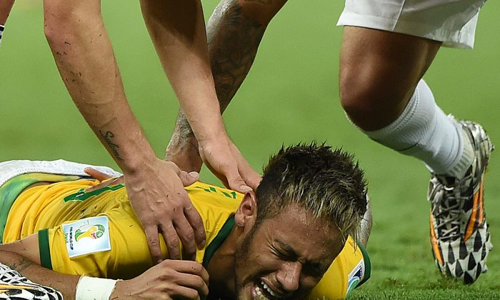 Brazil's forward Neymar (C) lies on the pitch after being injured during the quarter-final football match between Brazil and Colombia at the Castelao Stadium in Fortaleza during the 2014 FIFA World Cup on July 4, 2014. (EITAN ABRAMOVICH/AFP/Getty Images)