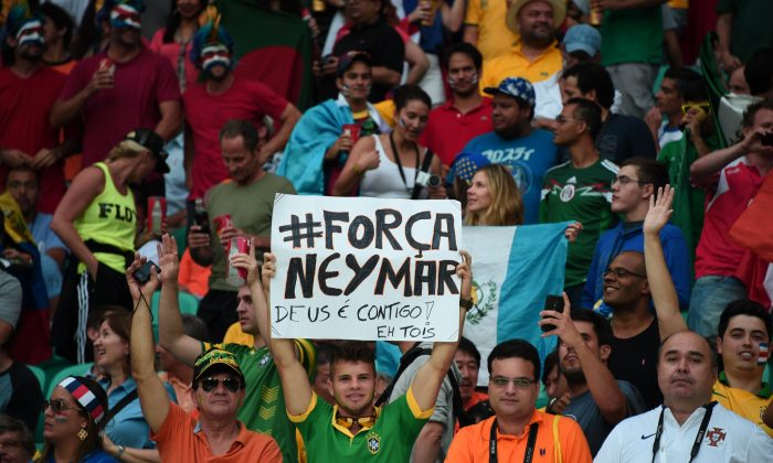 A Brazil's supporter holds a banner (reading : 'Be Strong Neymar, God is with You and Everybody') during a quarter-final football match between Netherlands and Costa Rica at the Fonte Nova Arena in Salvador during the 2014 FIFA World Cup on July 5, 2014. (DAMIEN MEYER/AFP/Getty Images)