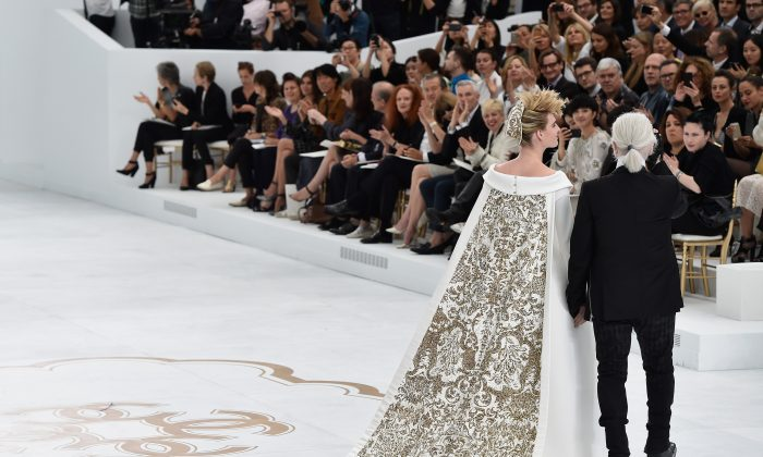 Fashion designer Karl Lagerfeld (R) and model Ashleigh Good (L) aknowledge the applause of the audience after the Chanel show as part of Paris Fashion Week - Haute Couture Fall/Winter 2014-2015 at Grand Palais on July 8, 2014 in Paris, France. (Photo by Pascal Le Segretain/Getty Images)