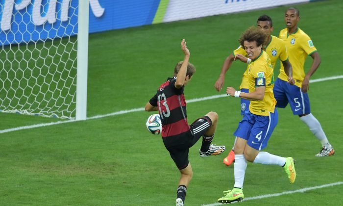 Germany's forward Thomas Mueller (L) scores his team's first goal during the semi-final football match between Brazil and Germany at The Mineirao Stadium in Belo Horizonte during the 2014 FIFA World Cup on July 8, 2014. (GABRIEL BOUYS/AFP/Getty Images)