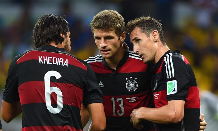Miroslav Klose of Germany (R) celebrates scoring his team's second goal with teammates Sami Khedira (L) and Thomas Mueller during the 2014 FIFA World Cup Brazil Semi Final match between Brazil and Germany at Estadio Mineirao on July 8, 2014 in Belo Horizonte, Brazil. (Laurence Griffiths/Getty Images)