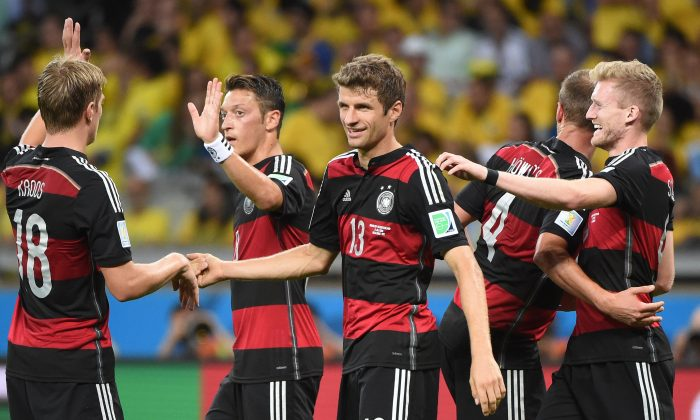 Germany's forward Andre Schuerrle (R) celebrates with (L-R) Germany's midfielder Toni Kroos, Germany's midfielder Mesut Ozil, Germany's forward Thomas Mueller and Germany's defender Benedikt Hoewedes after scoring his team's sixth goal during the semi-final football match between Brazil and Germany at The Mineirao Stadium in Belo Horizonte during the 2014 FIFA World Cup on July 8, 2014. (PATRIK STOLLARZ/AFP/Getty Images)