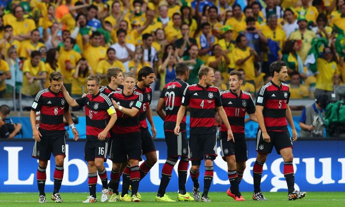 Thomas Mueller (3rd R) of Germany celebrates with his team-mates (L-R) Benedikt Hoewedes, Philipp Lahm, Bastian Schweinsteiger, Sami Khedira, Jerome Boateng, Benedikt Hoewedes, Miroslav Klose and Mats Hummels of Germany after scoring the opening goal during the 2014 FIFA World Cup Brazil Semi Final match between Brazil and Germany at Estadio Mineirao on July 8, 2014 in Belo Horizonte, Brazil. (Martin Rose/Getty Images)