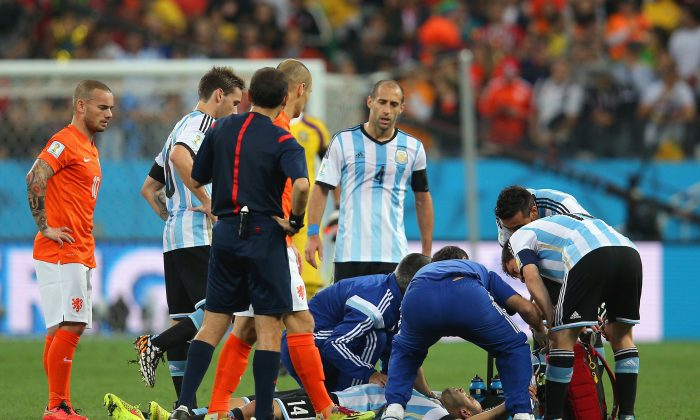 Javier Mascherano of Argentina receives treatment after a collision during the 2014 FIFA World Cup Brazil Semi Final match between the Netherlands and Argentina at Arena de Sao Paulo on July 9, 2014 in Sao Paulo, Brazil. (Photo by Dean Mouhtaropoulos/Getty Images)
