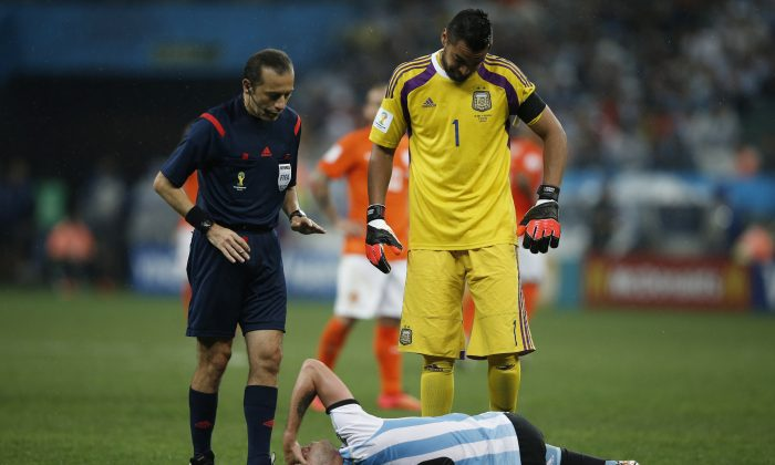 Argentina's midfielder Lucas Biglia (down) gestures in pain next to Turkish referee Cuneyt Cakir and Argentina's goalkeeper Sergio Romero during the semi-final football match between Netherlands and Argentina of the FIFA World Cup at The Corinthians Arena in Sao Paulo on July 9, 2014. (ADRIAN DENNIS/AFP/Getty Images)