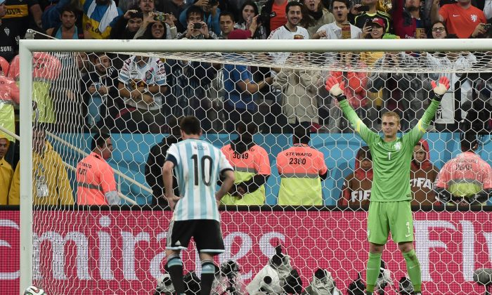 Argentina's forward and captain Lionel Messi (L) scores during a penalty shoot-out of the semi-final football match between Netherlands and Argentina of the FIFA World Cup at The Corinthians Arena in Sao Paulo on July 9, 2014. (DAMIEN MEYER/AFP/Getty Images)