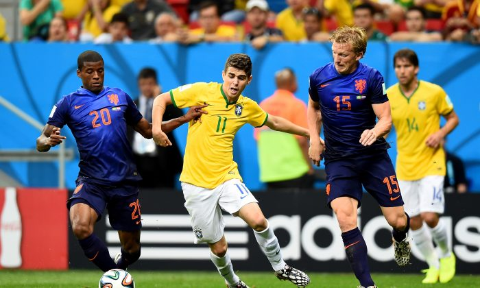 Oscar of Brazil is challenged by Georginio Wijnaldum (L) and Dirk Kuyt of the Netherlands during the 2014 FIFA World Cup Brazil Third Place Playoff match between Brazil and the Netherlands at Estadio Nacional on July 12, 2014 in Brasilia, Brazil. (Photo by Buda Mendes/Getty Images)