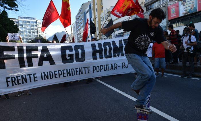 Demonstrators protest against the FIFA World Cup to demand better social services near the Maracana Stadium in Rio de Janeiro on July 13, 2014. Danny Schechter reports the World Cup left Brazil with large debts and intensified social tensions. (Yasuyoshi Chiba/AFP/Getty Images)