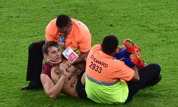 Security officials detain a pitch invader during the final football match between Germany and Argentina for the FIFA World Cup at The Maracana Stadium in Rio de Janeiro on July 13, 2014. (NELSON ALMEIDA/AFP/Getty Images)