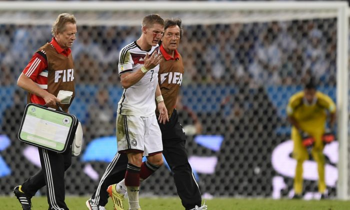 Germany's midfielder Bastian Schweinsteiger (C) is escorted of the pitch by medics after clashing with Argentina's forward Sergio Aguero (unseen) during the second half of extra-time during the 2014 FIFA World Cup final football match between Germany and Argentina at the Maracana Stadium in Rio de Janeiro, Brazil, on July 13, 2014. (FABRICE COFFRINI/AFP/Getty Images)