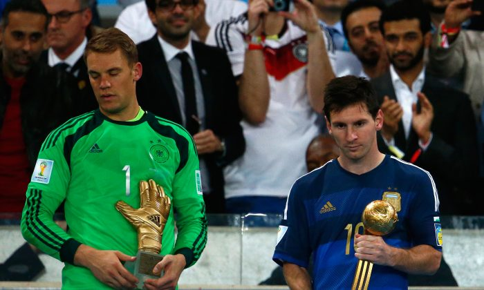 Manuel Neuer of Germany holds the Golden Glove trophy as Lionel Messi of Argentina holds the Golden Ball trophy during the 2014 FIFA World Cup Brazil Final match between Germany and Argentina at Maracana on July 13, 2014 in Rio de Janeiro, Brazil. (Clive Rose/Getty Images)