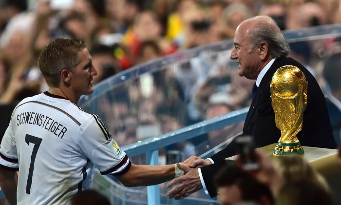 FIFA President Joseph Blatter (R) congratulates Germany's midfielder Bastian Schweinsteiger after the final football match between Germany and Argentina for the FIFA World Cup at The Maracana Stadium in Rio de Janeiro on July 13, 2014. (NELSON ALMEIDA/AFP/Getty Images)