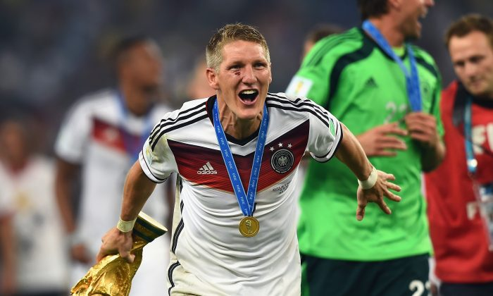 Bastian Schweinsteiger of Germany celebrates with the World Cup trophy after defeating Argentina 1-0 in extra time during the 2014 FIFA World Cup Brazil Final match between Germany and Argentina at Maracana on July 13, 2014 in Rio de Janeiro, Brazil. (Laurence Griffiths/Getty Images)