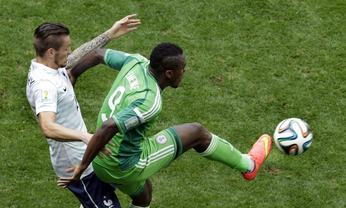 France's Mathieu Debuchy, left, and Nigeria's Emmanuel Emenike challenge for the ball during the World Cup round of 16 soccer match between France and Nigeria at the Estadio Nacional in Brasilia, Brazil, Monday, June 30, 2014. (AP Photo/Hassan Ammar)