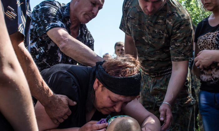 Relatives grieve over the body of Aleksandr Politov, a pro-Russia militia fighter who was killed when his group attacked a Ukrainian military checkpoint two days earlier in the village of Blahodatne, on May 24, 2014 in Horlivka, Ukraine. (Brendan Hoffman/Getty Images)