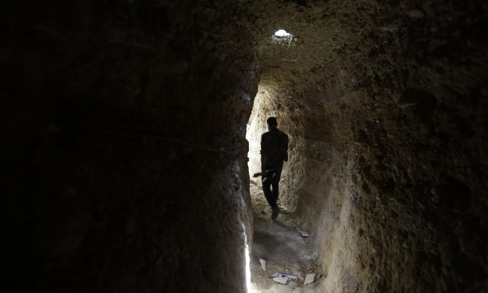 A Syrian army soldier makes his way in a tunnel reportedly previously used by rebel fighters in Jobar, a mostly rebel-held area on the eastern outskirts of Damascus on June 2, 2014. (Joseph Eid/AFP/Getty Images)