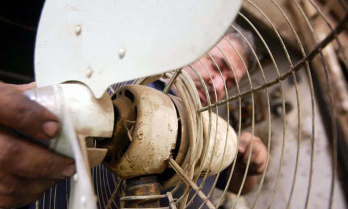 An Iraqi man repairs a fan at his shop in Baghdad, May 1, 2006. (Sabah Arar/AFP/Getty Images)