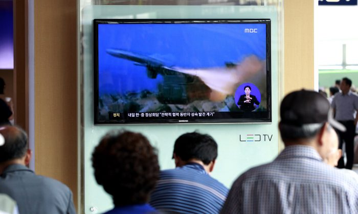People watch a TV news program showing a file footage of a missile launch conducted by North Korea, at Seoul Railway Station in South Korea on July 2, 2014. (AP Photo/Ahn Young-joon)