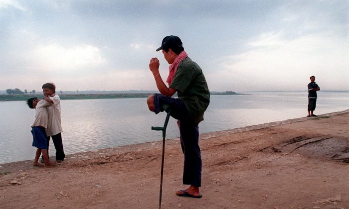 A Cambodian mine victim waiting for a hand-out from the next passing tourist rests on a crutch as he watches children scrap on the banks of the Tonle Sap River, Phnom Penh, April 9, 1999. (Rob Elliott/AFP/Getty Images)