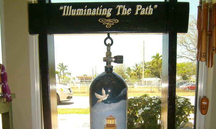 Scuba tank decorated with a lighthouse as a beacon. The work is titled 'Iuminating the Path,' and is on display at Prana in Key Largo, Florida. (Myriam Moran copyright 2014)