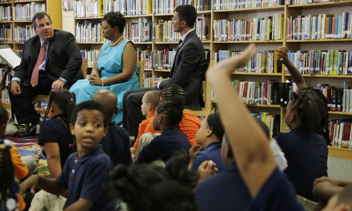 Elementary school students raise their hands to ask New Jersey Gov. Chris Christie (seated, L) a question, as Camden Mayor Dana Redd (seated, C) and Camden schools superintendent Paymon Rouhanifard (seated, R) look on, during a meeting at Riletta Twyne Cream school in Camden, N.J. on Sept. 10, 2013. New Jersey's state government has been giving a lot of attention to its poorest city, but some activists in Camden don't think the help is going to the right places. (Mel Evans/AP)
