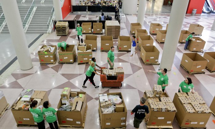 City Harvest volunteers consolidate for loading perishable items, which were donated by exhibitors at the end of the Summer Fancy Food Show convention on July 1. (Julie Jacobson/AP)