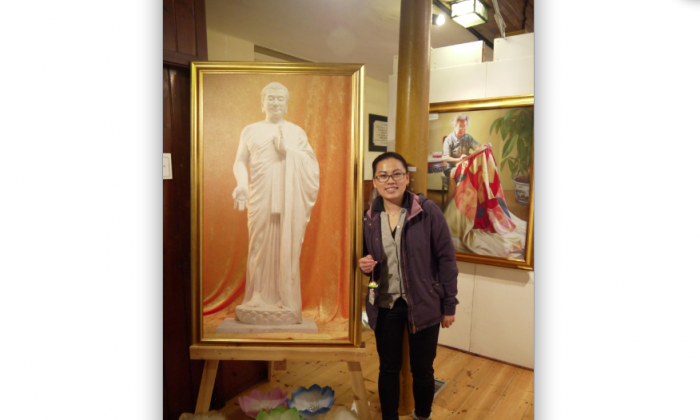 "A young Chinese woman from Hong Kong who said the The Art of Zhen Shan Ren Exhibition told ""A very sad story"". She is holding an origami lotus frequently given by Falun Dafa practitioners. The woman stands beside a picture of the Buddha statue by Kunlun Zhang and in front of Noble Task by Dong Xiqiang where a woman sews a banner before a parade. (Epoch Times)"
