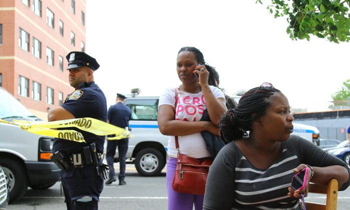 Leslie-Ann Robert Smith (R) sits outside of her Rockaway Parkway apartment building after lightning set it on fire overnight in Brownsville, Brooklyn, on July 4, 2014. (Brendon Fallon/Epoch Times)