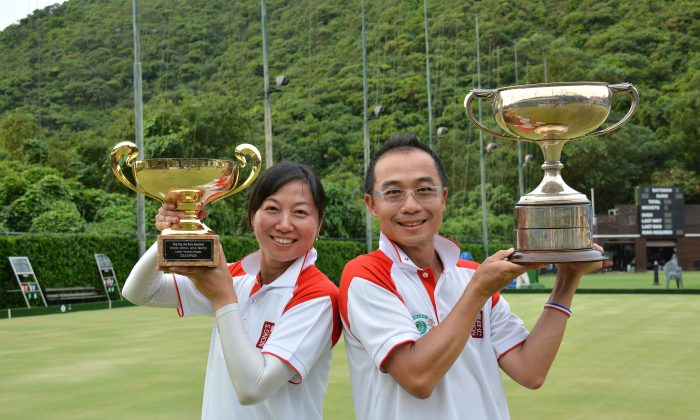 Hong Kong Football Club's Dorothy Yu (L) and Stanley Lai from Kowloon Bowling Green Club proudly display their Nong's National Singles trophy after prevailed in their respective finals on July 6, 2014. They each won prize money of HK$10,000, the highest ever in Hong Kong's lawn bowls competitions. (Stephanie Worth)