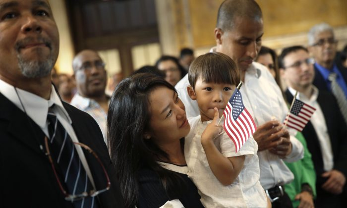 Miyoung Lee, (2nd from L), originally from Korea, holds her son Nate, 3, during a naturalization ceremony in the New York Public Library in New York, on July 2, 2014. (AP Photo/Seth Wenig)