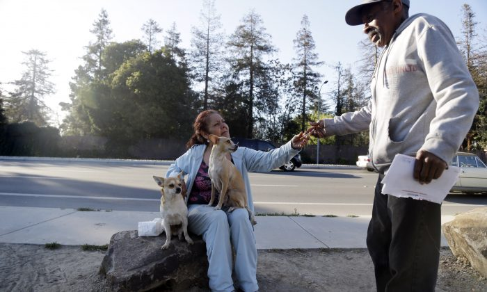 In this March 18, 2014, photo Maria Esther Salazar (C) grabs a cigarette from a friend in the Jungle, a homeless encampment in San Jose, Calif. The Jungle and several hundred smaller encampments in the region are the consequence of urban sprawl, with large open spaces that are not parks, and thus without rangers. (AP Photo/Marcio Jose Sanchez)