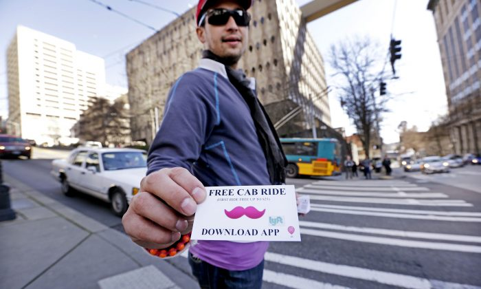 Jerad Bernard hands out cards to passers-by offering one free ride through the Lyft ridesharing service in Seattle, March 14. Beginning at 7 p.m. on Friday, residents in Brooklyn and Queens, N.Y. can hail a car from Lyft's 500-unit fleet on their smartphones. (AP Photo/Elaine Thompson)