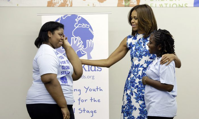 Jania Nelson (L) is overcome as she meets first lady Michelle Obama during her visit with members of Global Kids, at Baruch College, in New York, Thursday, July 10, 2014. Global Kids works to develop youth leaders through global education and leadership development programs. At right is Alaya Shearman. (AP Photo/Richard Drew)