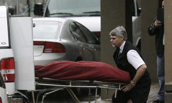 A coroner removes one of the bodies of six men from the scene of a multiple homicide in Surrey on Oct. 21, 2007. Cody Haevischer and Matthew Johnston are each charged with conspiracy and six counts of first-degree murder in the deaths of the men. (REUTERS/Lyle Stafford)