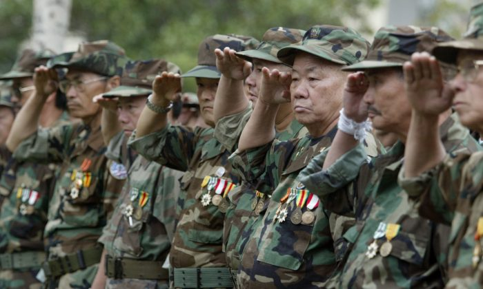 A group of Lao and Hmong veteran soldiers who fought in Vietnam and Loas salute during a ceremony to dedicate a new Lao Hmong American War Memorial at Courthouse Park in downtown Fresno, Calif. Dec. 21, 2005. (AP Photo/The Fresno Bee, Craig Kohrluss, File)