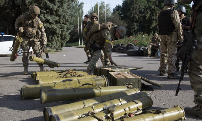 Ukrainian government army soldiers examine weapons captured from rebels in the city of Slovyansk, Donetsk Region, eastern Ukraine on July 5, 2014. By late afternoon on Saturday, Ukrainian troops were fully in control of rebel headquarters in Slovyansk, a city of about 100,000 that has been a center of the fighting between Kiev's troops and the pro-Russia insurgents. (AP Photo/Dmitry Lovetsky)