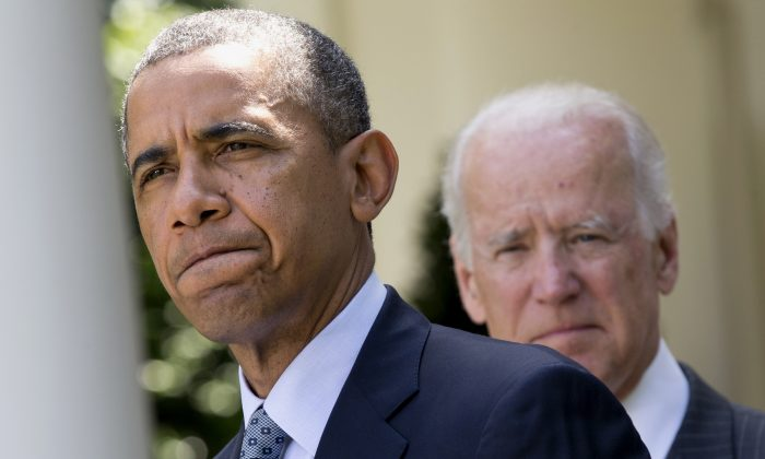 President Barack Obama, accompanied by Vice President Joe Biden, pauses while making an announcement about immigration reform, Monday, June 30, 2014, in the Rose Garden of the White House in Washington. The president said he's done waiting for House Republicans to act on immigration. He says he now plans to act on his own. Obama announced his intention Monday to take executive action.  (AP Photo/Jacquelyn Martin)