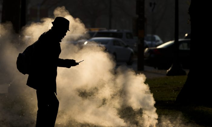FILE - In this Nov. 30, 2012 file photo, a pedestrian looks at his phone near steam vented from a grate near the Philadelphia Museum of Art on a cold morning in Philadelphia.  A study released Thursday, July 3, 2014 by the journal Science, which involved college students who left their cellphones and other distractions behind to be alone to think for six to 15 minutes, found that many of them reported it wasn't very fun. (AP Photo/Matt Rourke, File)