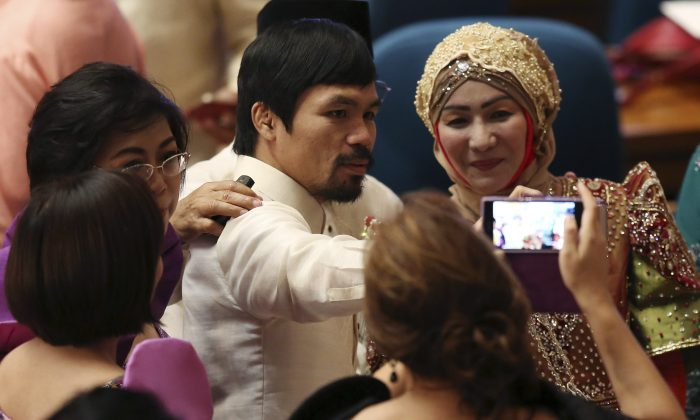 Philippine congressman and boxing hero Manny Pacquiao, top center, has his pictures taken with fellow representatives before the start of the 5th State of the Nation Address by President Benigno Aquino III during the joint session of the 16th Congress at the House of Representatives in suburban Quezon city, north of Manila, Philippines Monday, July 28, 2014. (AP Photo/Aaron Favila)
