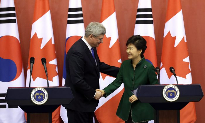Prime Minister Stephen Harper shakes hands with South Korean President Park Geun-hye on March 11, 2014, in Seoul after reaching a free trade agreement that the two governments hope will boost exports and investment. Recent immigrants are exporting more outside the United States compared to their Canadian counterparts, a new study has found. (AP Photo/Lee Jin-man, Pool)