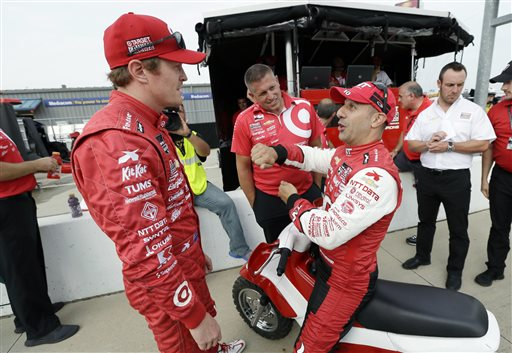 Scott Dixon talks with Tony Kanaan, right, after qualifying at the IndyCar Series' Iowa Corn Indy 300 auto race, Friday, July 11, 2014, at Iowa Speedway in Newton, Iowa. Dixon won the pole position for Saturday night's race. (AP Photo/Charlie Neibergall)