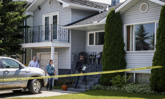 Police investigators check out the Calgary home of Alvin and Kathryn Liknes, who went missing with their 5-year-old grandson Nathan O'Brien on June 29, 2014. (The Canadian Press/Jeff McIntosh)