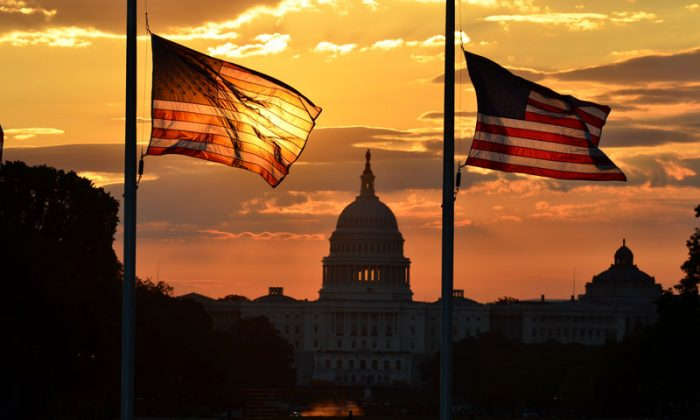 United States Capitol building silhouette and U.S. flags at sunrise. (Shutterstock*)
