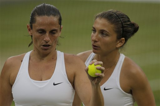 Sara Errani of Italy, right, and Roberta Vinci of Italy talk between points during their women's doubles final against Timea Babos of Hungary and Kristina Mladenovic of France at the All England Lawn Tennis Championships at Wimbledon, London, Saturday July 5, 2014.  (AP Photo/Pavel Golovkin)
