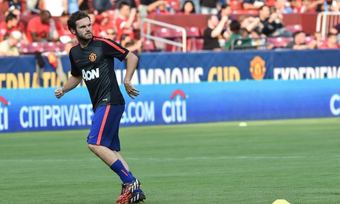 Manchester United's Juan Mata (R) warms up before a Champions Cup match against Inter Milan at FedEx Field in Landover, Maryland, on July 29, 2014. (NICHOLAS KAMM/AFP/Getty Images)