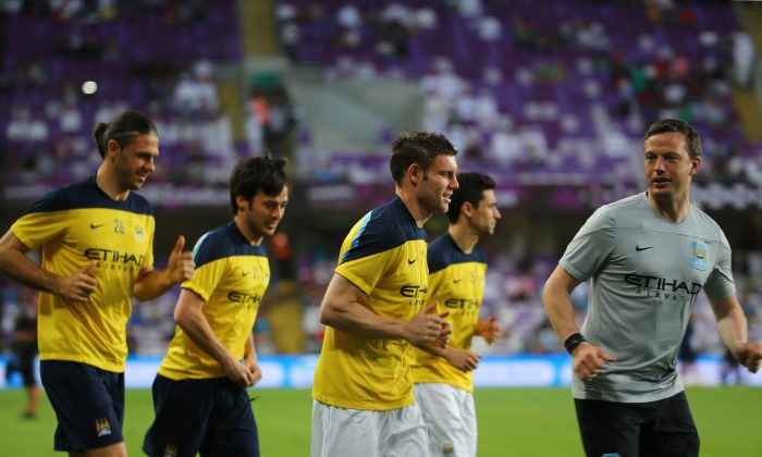 Martin Demichelis (L), James Milner (C-front), David Silva (2L) and Jesus Navas (C-back) from newly-crowned English Premier League champions Manchester City football team warm up prior to their friendly football match against UAE's Al-Ain club at the Mohammed bin Zayed Stadium in Al-Ain on May 15, 2014. (MARWAN NAAMANI/AFP/Getty Images)