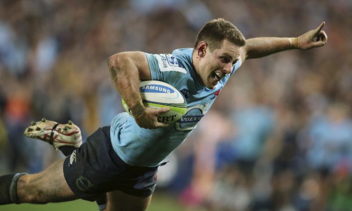 The Waratahs' Bernard Foley begins to celebrate just before scoring a try agains the Brumbies during their Super Rugby semifinal match in Sydney, Saturday, July 26, 2014. The Waratahs won the match 26-8. (AP Photo/Rick Rycroft)