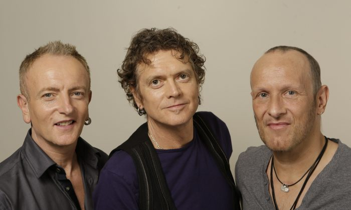 """In this photo taken Wednesday, Sept. 25, 2013, British rock group, Def Leppard, from left, Phil Collen, Rick Allen and Vivian Campbell pose for a photo in Los Angeles. First up, in a year of firsts for the band, is the special-event screening Wednesday, Oct. 1, 2013, (and again on Oct. 8) of their live concert film at theaters nationwide """"Def Leppard Viva! Hysteria Concert."""" (AP Photo/Damian Dovarganes)"""