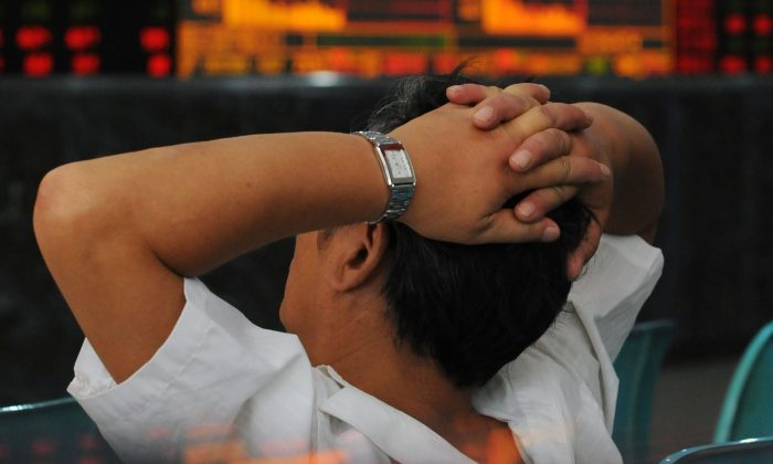 An investor looks at stock quotes in Wuhan, China, Sept. 16, 2008. (China Photos/Getty Images)